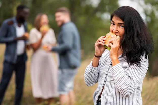 ハンバーガーを食べるミディアムショットの女性 Premium写真