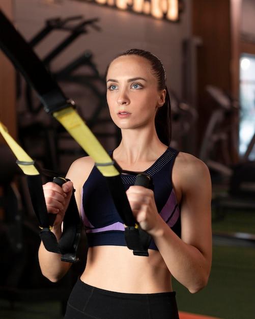 Женщина среднего выстрела, тренирующаяся в тренажерном зале Бесплатные Фотографии