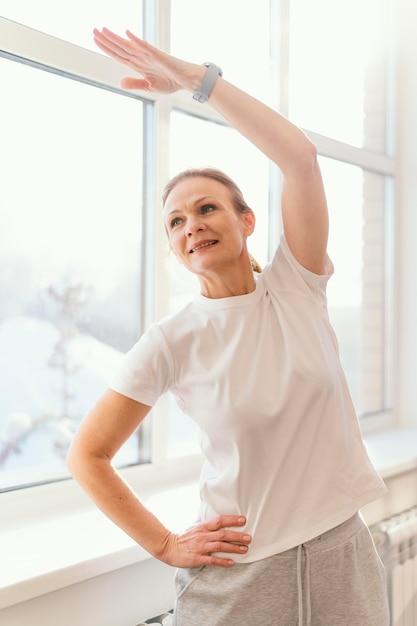 屋内で運動するミディアムショットの女性 無料写真