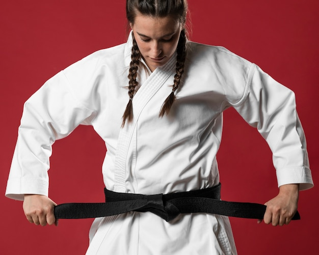 Medium shot of woman fighter straighten her belt Free Photo