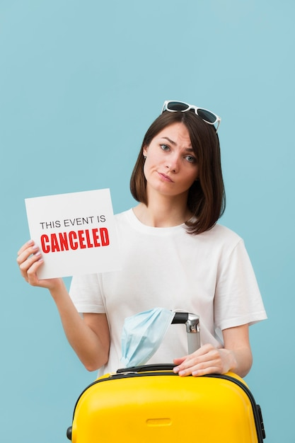 Medium shot woman holding a card with a canceled event message Free Photo