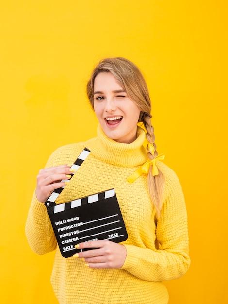 Medium shot woman holding clapboard Free Photo