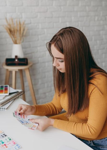 색상 팔레트 카드를 들고 중간 샷된 여자 프리미엄 사진