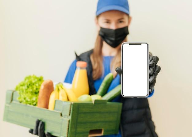Средний выстрел женщина, держащая ящик с едой Бесплатные Фотографии