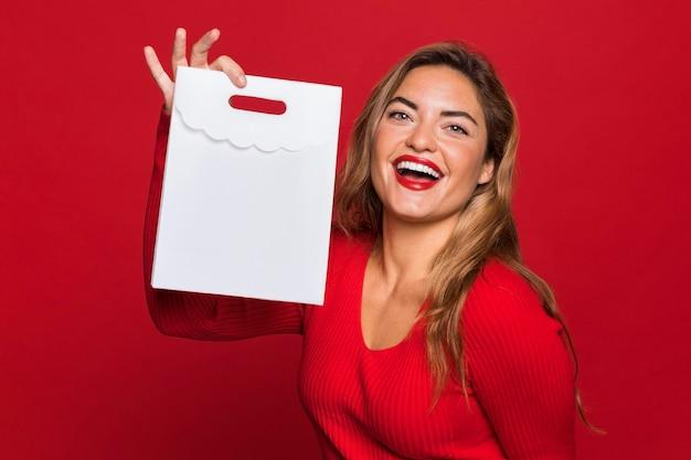 종이 가방을 들고 중간 샷된 여자 무료 사진