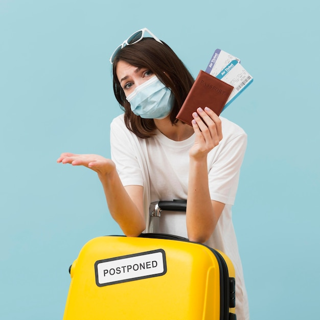 Средний выстрел женщина держит билеты на самолет и желтый багаж Premium Фотографии