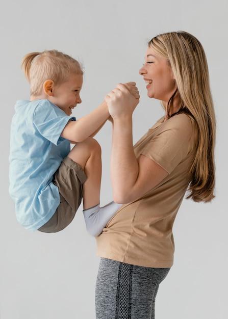 웃는 아이 들고 중간 샷 여자 무료 사진