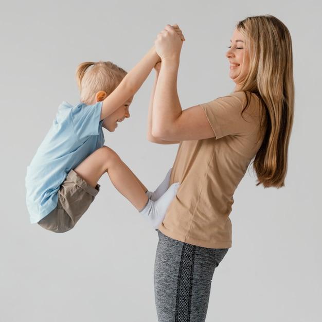 웃는 아이 들고 중간 샷된 여자 무료 사진