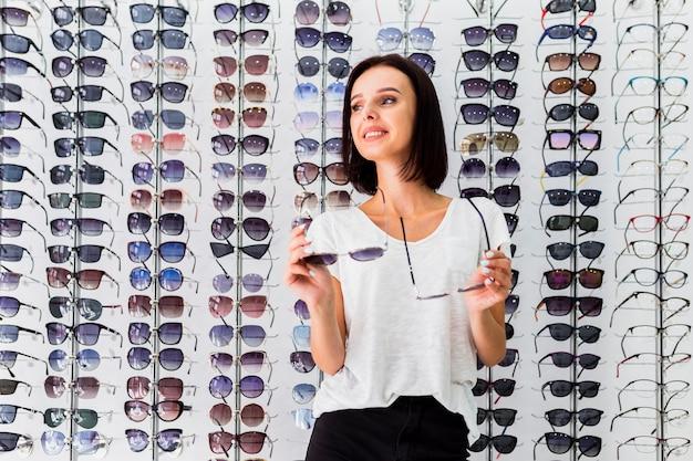 Medium shot of woman holding sunglasses pairs Free Photo