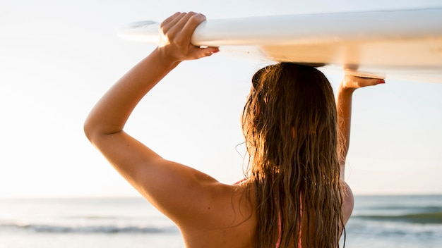 Medium shot woman holding surf board Free Photo