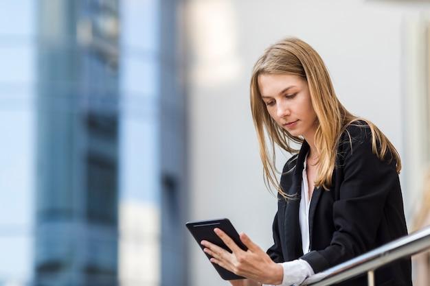 Medium shot woman holding a tablet Free Photo