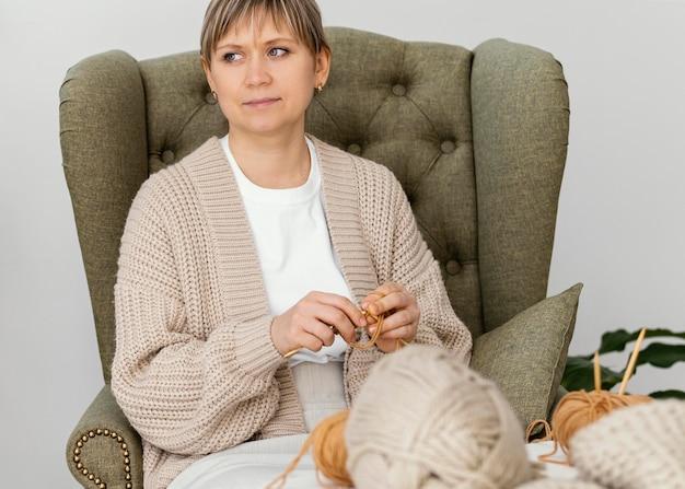 중간 샷 여자 뜨개질 및 멀리보고 무료 사진