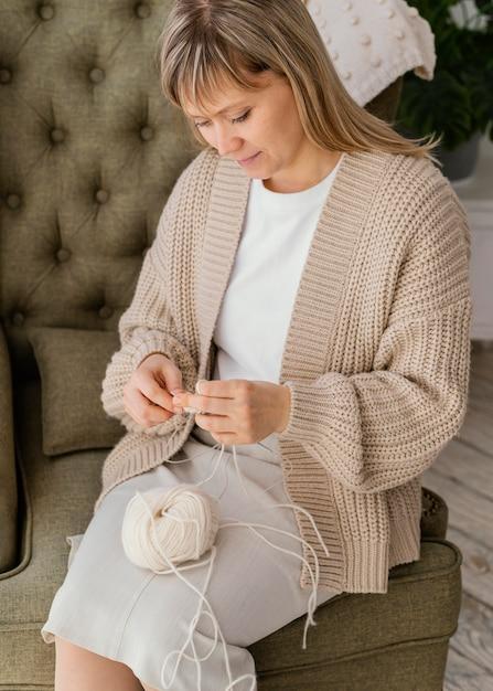 Colpo medio donna che lavora a maglia alto angolo Foto Gratuite