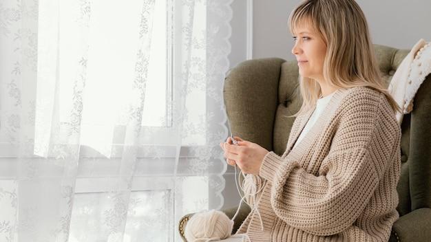 창 근처 뜨개질 중간 샷된 여자 무료 사진