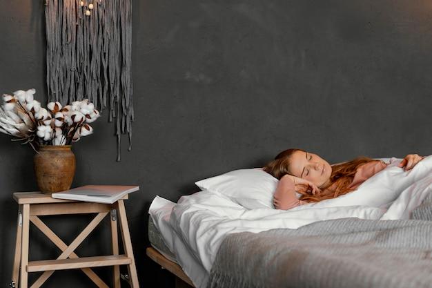 Женщина среднего выстрела, лежа на кровати Бесплатные Фотографии