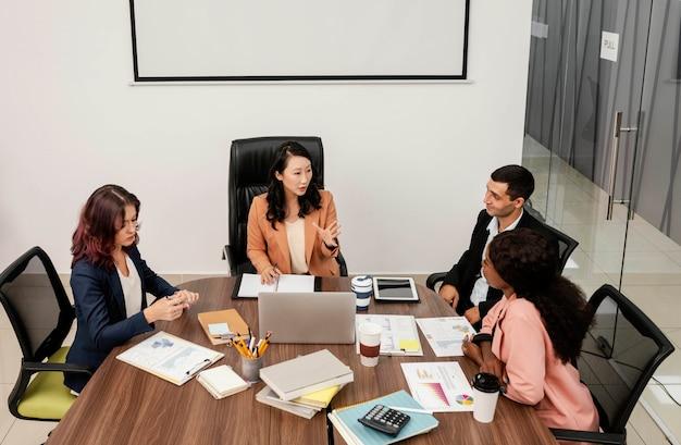 デスクでチームを率いるミディアムショットの女性 Premium写真