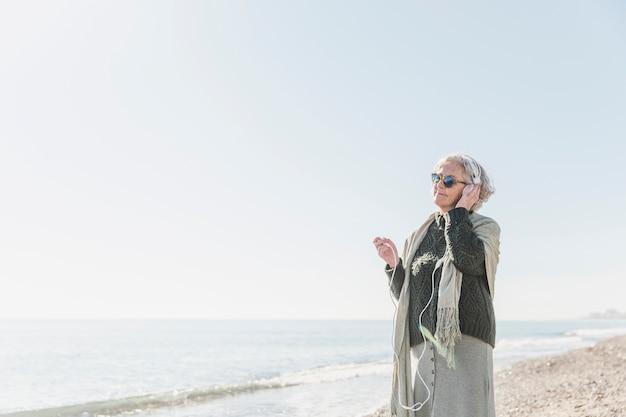 屋外で音楽を聴くミディアムショット女性 無料写真