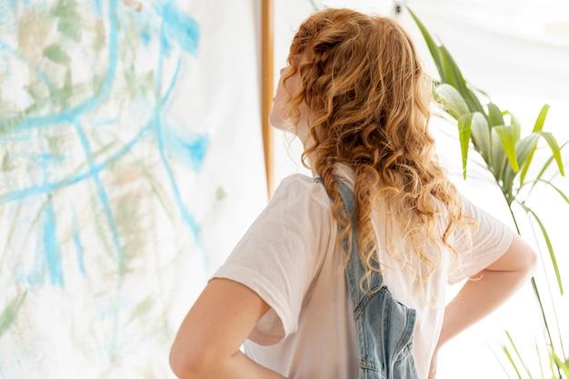 Среднего выстрела женщина смотрит на стену Бесплатные Фотографии