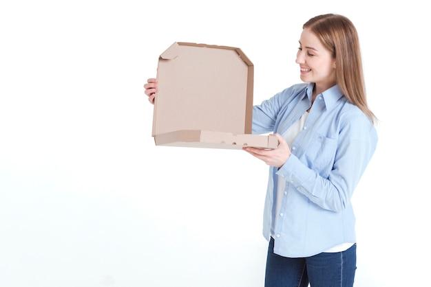 Medium shot of woman looking into a pizza box Free Photo