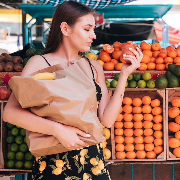 Medium shot woman looking at a pomegranate Free Photo