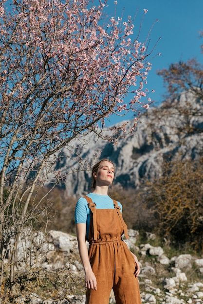 Medium shot woman in overall under blooming tree Free Photo