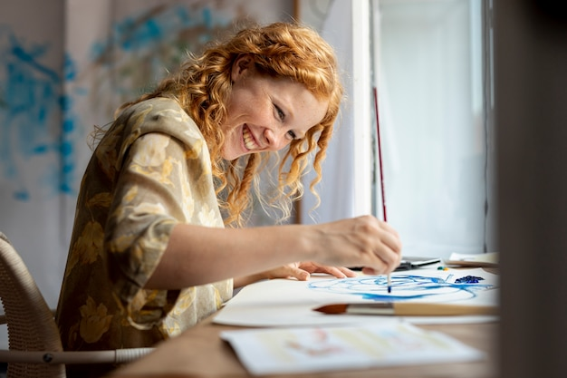 Medium shot woman painting happily Free Photo