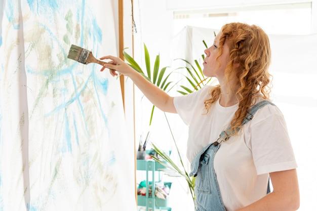 Средний снимок женщины, рисующей на стене Бесплатные Фотографии