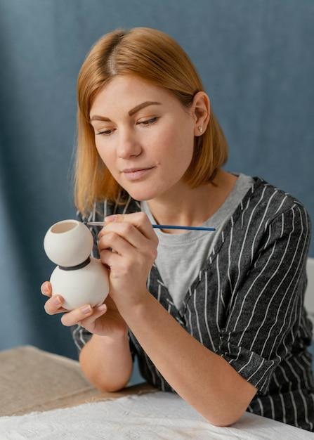 Oggetto di ceramica pittura donna colpo medio Foto Gratuite