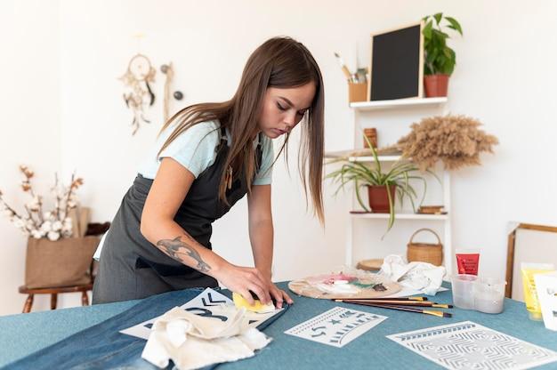 スポンジで絵を描くミディアムショットの女性 無料写真