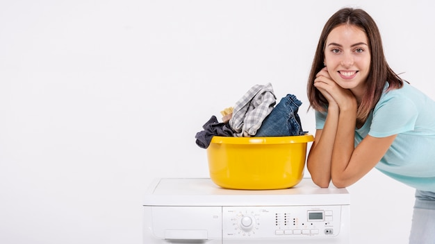 Medium shot woman posing near laundry basket Free Photo