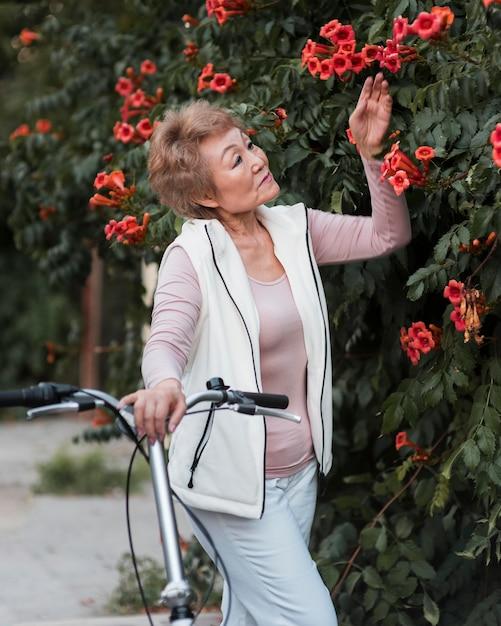 花でポーズをとるミディアムショットの女性 無料写真