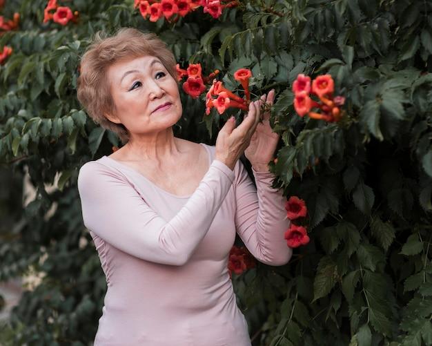 きれいな花でポーズをとるミディアムショットの女性 無料写真