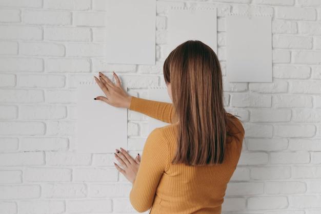 중간 샷 여자 종이 벽에 퍼팅 무료 사진