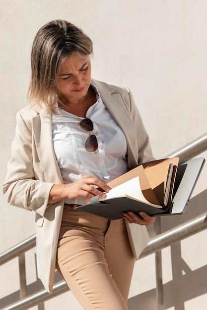 Женщина среднего кадра читает документы Бесплатные Фотографии