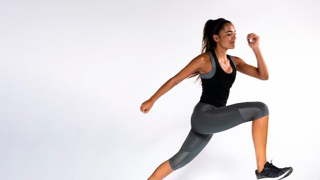 屋内で走っているミディアムショットの女性 Premium写真
