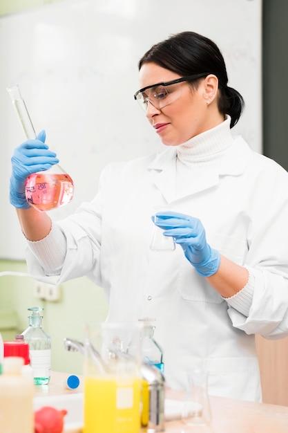 Scienziato della donna del colpo medio con la boccetta Foto Gratuite