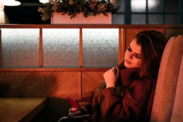 Donna del colpo medio che si siede al tavolo Foto Gratuite