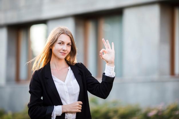 Средний выстрел женщина улыбается и показывает одобрение Бесплатные Фотографии