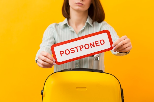 Medium shot woman standing next to her luggage while holding a postponed sign Free Photo