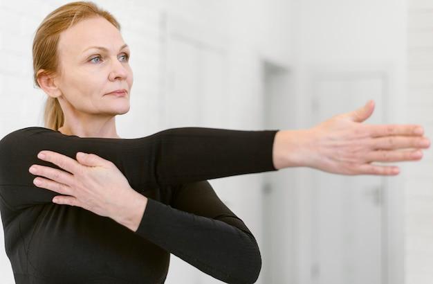 ミディアムショットの女性が腕を伸ばす 無料写真