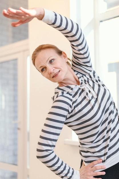 屋内でストレッチするミディアムショットの女性 無料写真
