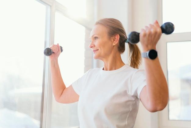 屋内でトレーニングするミディアムショットの女性 無料写真