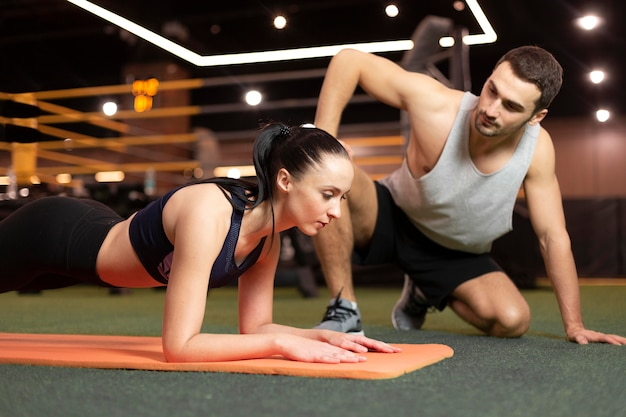 Средний план тренировки женщины на коврике Бесплатные Фотографии