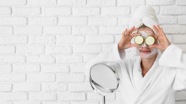 Donna del colpo medio che prova il trattamento del viso Foto Gratuite