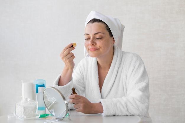 Colpo medio donna che utilizza siero Foto Gratuite