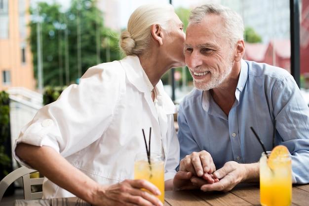 Medium shot woman whispering in man's ear Free Photo