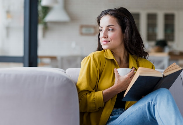 Medium shot woman with book and cup Free Photo