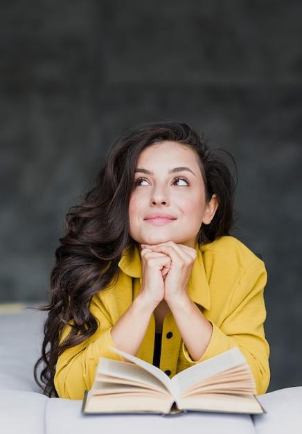 Medium shot woman with book thinking Free Photo