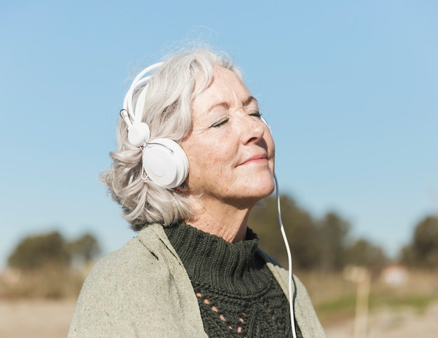 Medium shot woman with closed eyes and headphones Free Photo