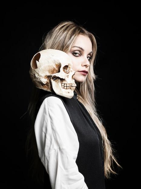 Medium shot of woman with cranium on shoulder Free Photo